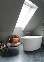 A free-standing bathtub and chair in an attic bathroom