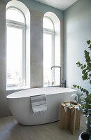 A freestanding bathtub with a freestanding tap in front of an arched window