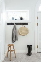 Wooden stool, coat rack, and boots in the hall