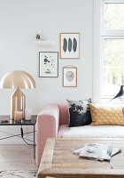 Pink upholstered suite, golden table lamp, and rustic coffee table in the living room