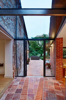 View onto patio area from extension, featuring a glass ceiling between the old farmhouse and contemporary extension