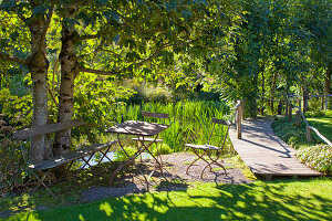 Seating area next to jetty on lake in sunny garden