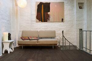 Sofa unterm Bild neben dem Absatz zur Wendeltreppe
