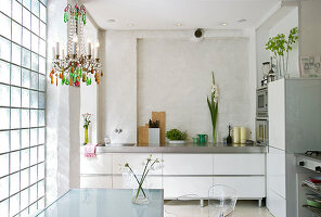 Chandelier above the dining table on the glass block wall in a modern kitchen