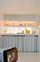 Curtains as fronts in a small kitchen with brick shelves