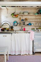 The curtain over the sink in a small kitchen with open shelves