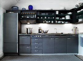 An anthracite-coloured kitchen with black open shelves above it