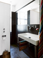 A square washbasin in a small bathroom with dark tiles