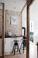 A breakfast bar with bar stools in front of a brick wall in an open-plan kitchen with wooden supports