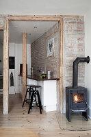 Kaminofen in Zimmerecke, Blick in Küche mit Frühstückstheke vor Ziegelwand