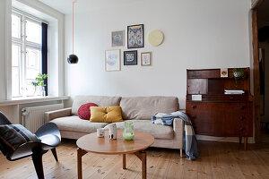Antiker Sekretär, sandfarbene Couch, Coffeetable und Designerstuhl im Wohnzimmer