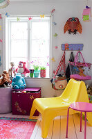 A yellow plastic chair, bags and stuffed animals at the window in a children's room