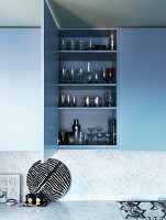 Open wall cabinet with glasses in the kitchen with blue fronts