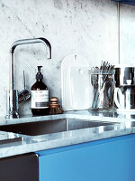Sink and splash guard made of marble in the kitchen with blue cabinet fronts