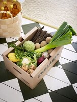 Various fresh vegetables in an organic crate on a chequered floor