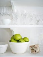 Green pears in a bowl on a kitchen shelf with glasses