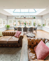 Chesterfield sofa and dining table below skylight in open-plan interior