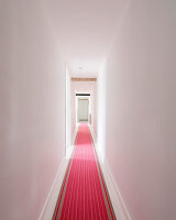 Long, white hallway with red runner in converted barn