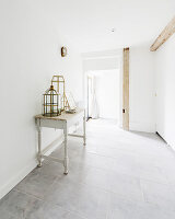 Lanterns on antique console table in white hallway of converted barn