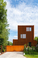 Modern architect-designed house with open facade of rusty metal
