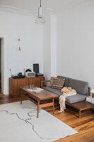 Retromöbel im schlichten Wohnzimmer mit Stuckdecke