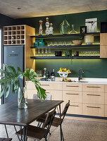 Regale mit indirekter Beleuchtung an grüner Wand in der Wohnküche