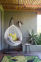 Hanging chair on roofed terrace in Urban Jungle style