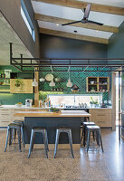 Metal stools around high table in open-plan kitchen in shades of grey and green