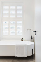 Modern, free-standing bathtub below window with shutters