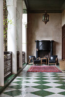 Sessel vorm offenen Kamin auf der Loggia mit Schachbrettboden