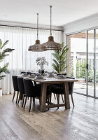 Set dining table next to terrace doors in open-plan interior