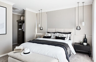 Double bed with tall headboard, pendant lamps above bedside tables and view into dressing area in elegant bedroom
