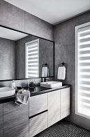 Elegantes Badezimmer mit Waschtischmöbe und grauen Wandlfiesen