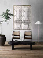 Organisch geformter Couchtisch, zwei Stühle, Stehleuchte und Zimmerpflanze, an Wand moderne Kunst