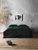 Doppelbett mit grüner Tagesdecke und Stehleuchte vor grauer Wand