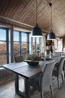 Dining table next to lattice windows of cottage with view over imposing landscape