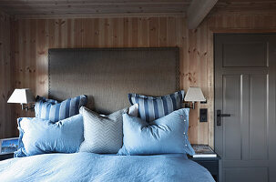 Bed with grey headboard and blue bed linen against wooden wall in cottage bedroom