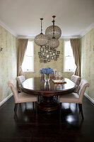 Anitker, ovaler Esstisch mit hellen Polsterstühlen und Hängelampen im Esszimmer mit Tapete
