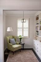 Grün-gelber Ohrensessel, Stehlleuchte und Beistelltisch, gegenüber Regalwand im Wohnzimmer