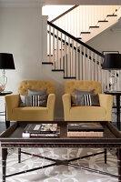 Pastellfarbene Polstersessel und Couchtisch im Wohnzimmer vor Treppe