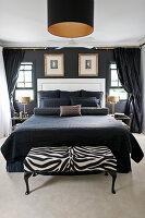 Doppelbett mit schwarzen Accessoires und weißem Betthaupt im Schlafzimmer mit schwarzer Wand, Kleiderbank in Zebra-Look