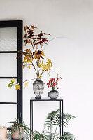 Zweige mit Herbstlaub und Hagebutten in Vasen