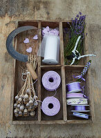 Lavender flowers, poppy seed heads and decorative materials in rustic divided tray