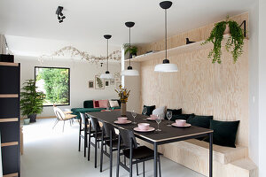 Long, black dining table with chairs and fitted wooden bench