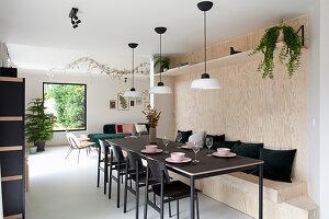 Länglicher schwarzer Esstisch mit Stühlen und eingebauter Holzbank
