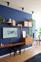 Wohnwand im Mid Century Stil an blauer Wand im Wohnzimmer