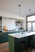 Barstools at island counter in kitchen with dark green cupboards