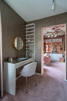 Dressing table against glittery wallpaper and view of bookcase in girl's bedroom