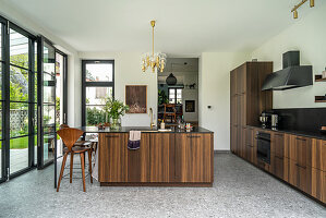 Elegant, custom kitchen and island counter with wooden fronts and terrace doors