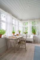 Desk below conservatory windows with airy curtains